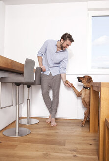 Man with his Rhodesian Ridgeback in the kitchen - MFRF000579
