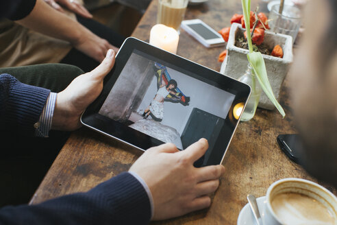 Man in a cafe showing picture on digital tablet to friends - JUBF000125