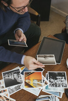 Man in a cafe looking at photo prints - JUBF000128
