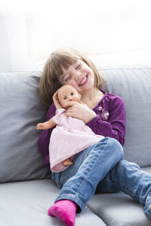Portrait of happy little girl sitting with her doll on the couch - LVF004698