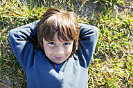 Portrait of smiling boy sitting in meadow - VABF000414