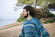 Young man with dreadlocks smiling and shaking his head - KIJF000287