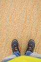 UAE, Rub' al Khali, man standing in the desert sand, partial view - MAUF000389