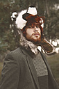 Portrait of redheaded young man wearing raccoon hat in the woods - RTBF000068
