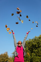Young woman throwing autumn leaves in the air - KLR000289