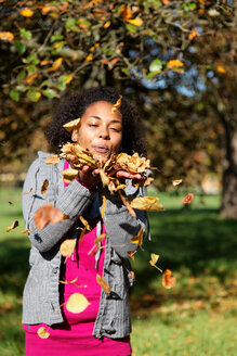 Young woman blowing autumn leaves in the air - KLR000292