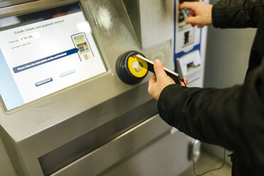 UK, London, man buying cashless a ticket at ticket machine - MGOF001683