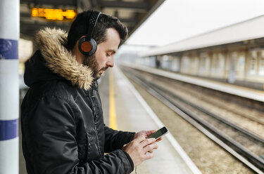 Man with headphones standing on platform using his smartphone - MGOF001686