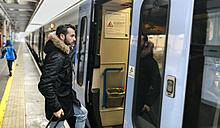 London, UK, man at railway station boarding a train - MGO001689