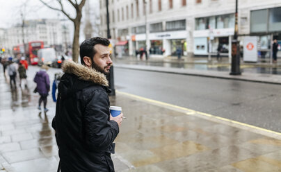 UK, London, man with coffee to go on a rainy day - MGOF001692