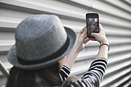 Back view of young woman taking a selfie with smartphone - RTBF000083