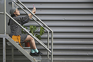 Young woman sitting onb stairs taking a selfie with smartphone - RTBF000086