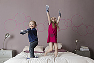 Two siblings playing with socks on their parents' bed - LITF000225