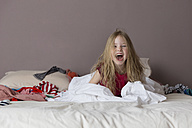 Laughing little girl sitting on parents' bed playing with a sheet - LITF000237