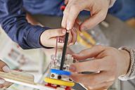 Hands assembling plastic cogwheels - RHF001377