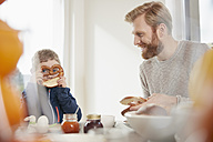 Father and playful son with pretzel having breakfast - RHF001386