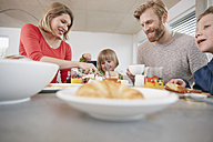 Happy family of four having breakfast - RHF001389