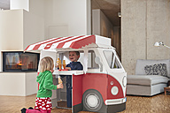 Brother and sister with popsicles and model ice cream van in living room - RHF001410