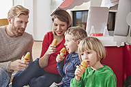 Happy family with popsicles and model car in living room - RHF001413