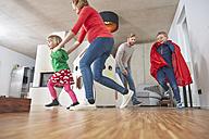 Happy family running in living room - RHF001416
