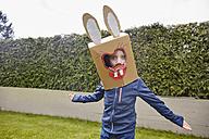Boy wearing bunny mask in garden - RHF001422