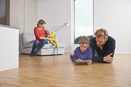 Fathar and son with digital tablet lying on floor - RHF001434