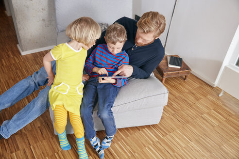 Father and two children using digital tablet - RHF001440