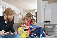 Family of four using mobile devices on couch - RHF001455