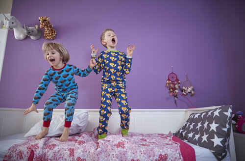Brother and sister wearing pajamas romping around in children's room - RHF001467