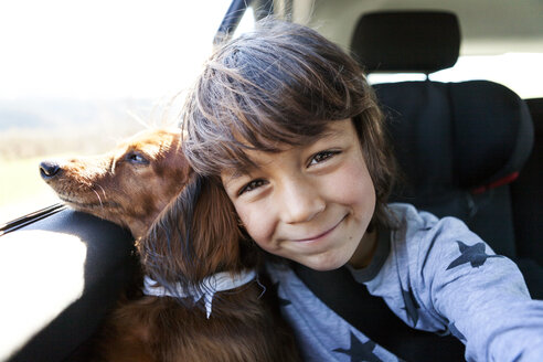 Portrait of smiling little boy sitting with his long-haired dachshund in a car - VAB000418