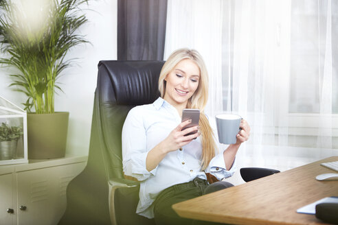 Portrait of smiling blond woman sitting at her desk withcup of coffee looking at her smartphone - SEGF000489