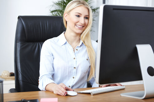 Portrait of smiling blond woman working at desk - SEGF000498
