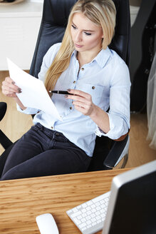 Blond woman sitting at desk checking documents - SEGF000501