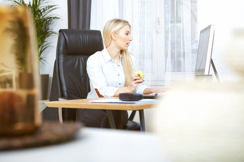 Blond woman sitting at desk in her home office eating an apple - SEGF000507