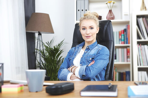 Portrait of confident blond businesswoman sitting at desk in her home office - SEGF000510