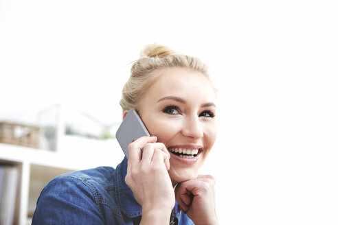 Portrait of smiling blond woman telephoning with smartphone - SEGF000516
