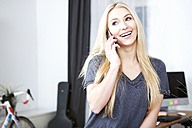 Portrait of smiling blond woman telephoning with smartphone at home - SEGF000525