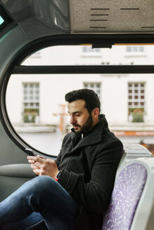 Young man in a double-decker bus using his smartphone - MGOF001697