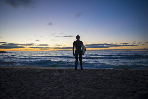 Back view of surfer standing on the beach at sunrise - SKCF000080