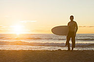 Surfer standing on the beach at sunrise - SKCF000086