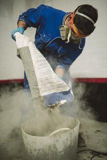 Bricklayer pouring cement powder in bucket - RAEF001010