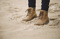 Woman wearing bbots standing in the sand, partial view - RAEF001021
