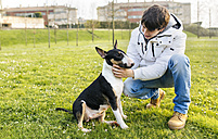 Young man with his bull terrier on a meadow - MGOF001704