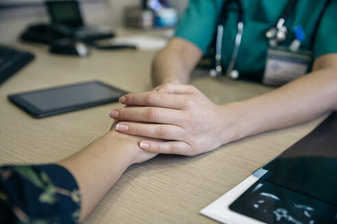 Doctor holding patient's hand on table - DAPF000073