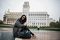 Spain, Barcelona, smiling young woman sitting  on Placa Catalunya looking at cell phone - JRFF000517