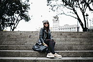 Spain, Barcelona, smiling young woman sitting on stairs - JRFF000520