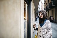Spain, Barcelona, smiling young woman in the city looking at shop window - JRFF000523