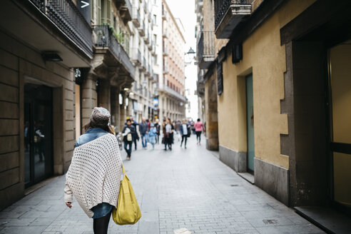 Spain, Barcelona, young woman walking in an alley - JRFF000532