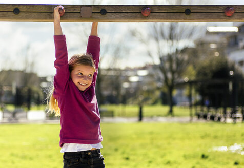 Portrait of smiling little girl playing on a playground - MGOF001707