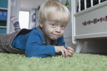 Portrait of funny little blond boy lying on green carpet at home - RBF004244